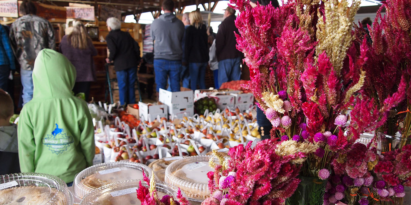 Chesterhill Produce Auction page header featuring event with apples, baked goods and flowers.